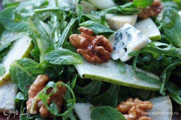 Полить салат заправкой, перемешать, сверху разложить орехи.