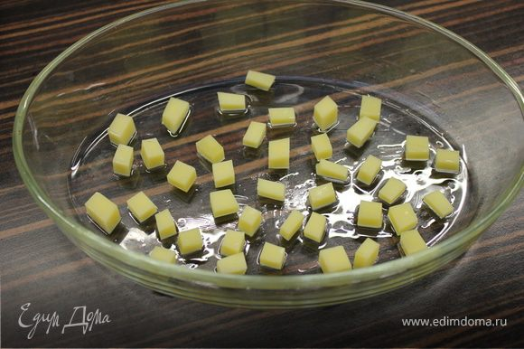 Форму для запекания смазать маслом и выложить на дно кубики сыра.