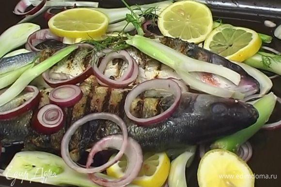 На дно противня уложить половину нарезанного лука, фенхеля и лимона, сверху разложить обжаренную рыбу, полить оливковым маслом и белым вином, а затем выложить оставшийся лук, фенхель и лимоны. Запекать 20 минут в разогретой духовке.