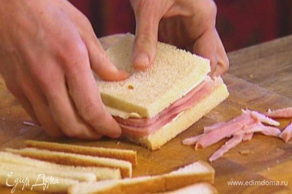 С хлеба срезать корки, на один кусок выложить ломтик сыра, затем 2 ломтика ветчины и снова сыр. Накрыть вторым куском хлеба, срезать лишние края.