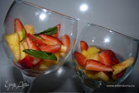 Ананас очистить, порезать на кусочки, клубнику также порезать. Выложить в креманки или бокалы, полить ликёром, украсить листиками мяты. Для детей фрукты полить жидким мёдом.