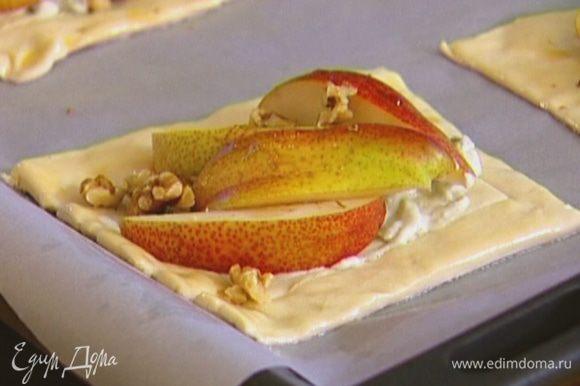 Выложить сырную начинку в центр квадратиков из теста, сверху положить дольки груш, добавить несколько капель кленового сиропа, посыпать орехами, посолить и поперчить.