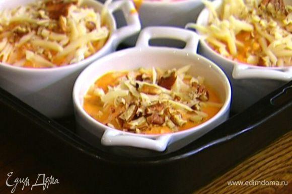 Разложить тыквенную массу в небольшие керамические формочки, присыпать сыром и оставшимися орехами.