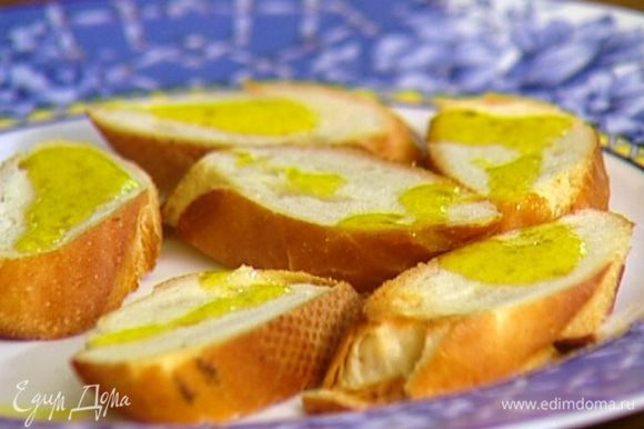 Горячие гренки натереть чесноком и сбрызнуть оставшимся оливковым маслом.