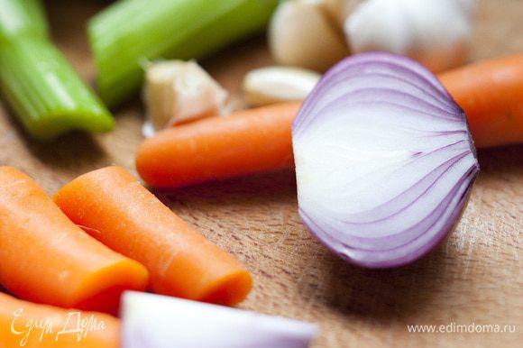Морковь, луковицу и зубчик чеснока для бульона почистить, крупно нарезать и отправить в кастрюлю, добавить разрезанный на несколько частей стебель сельдерея, майоран, лавровый лист, перец горошком и соль, залить все водой и сварить овощной бульон.