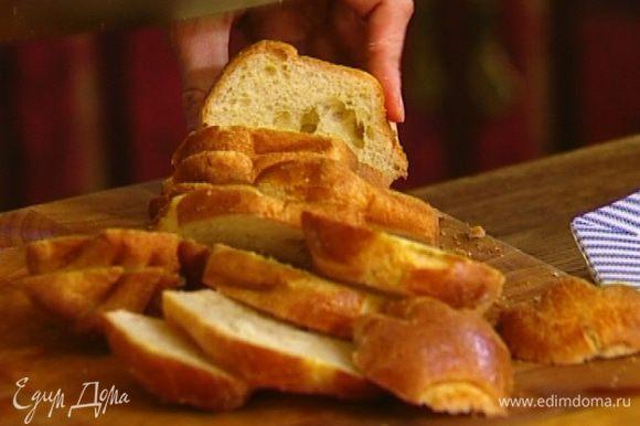 Булочки нарезать ломтиками и выложить плотным слоем в форму, смазанную оливковым маслом.
