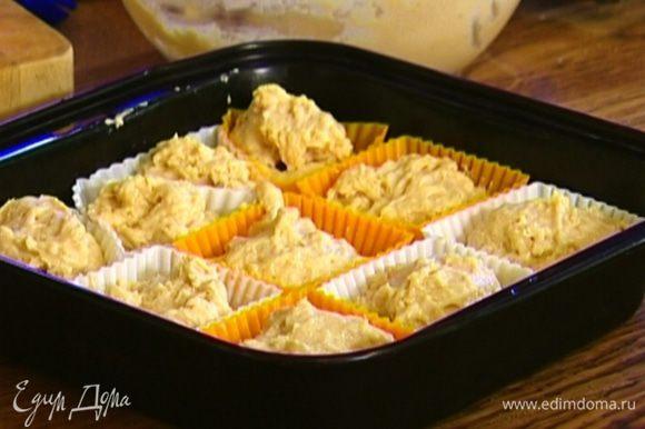 Формочки для маффинов смазать растительным маслом, заполнить их тестом на 1/3 объема, положить в каждую кусочек хурмы или клубнику, а затем добавить еще теста — практически до верха.