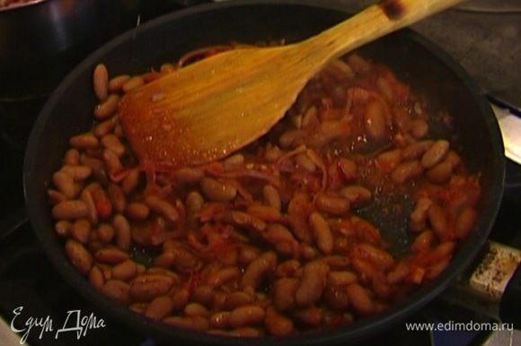 Когда соус немного уварится, выложить в сковороду отваренную фасоль, посолить, поперчить и, постоянно помешивая, обжаривать несколько минут.