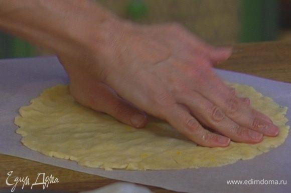 Нарисовать на листе бумаги для выпечки круг диаметром чуть больше разъемной формы и равномерно распределить в этом круге оставшееся тесто, чтобы получилась «крышечка» для пирога. Отправить форму и бумагу с тестом на 20−30 минут в холодильник.