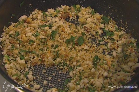 Булку измельчить в блендере в крошку, выложить к анчоусам с чесноком, добавить петрушку.