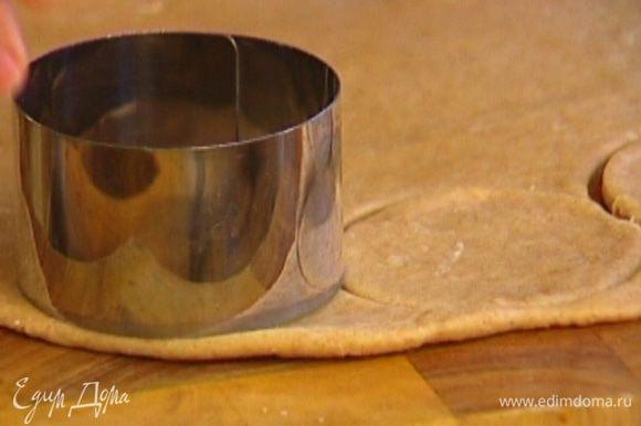 Вырезать формочкой или стаканом из теста кружки, а затем сделать в них выемки посередине с помощью формочки меньшего диаметра.