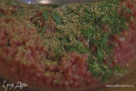 Добавить в фарш 1 яйцо, половину измельченной зелени, орегано, по щепотке соли и перца и перемешать.