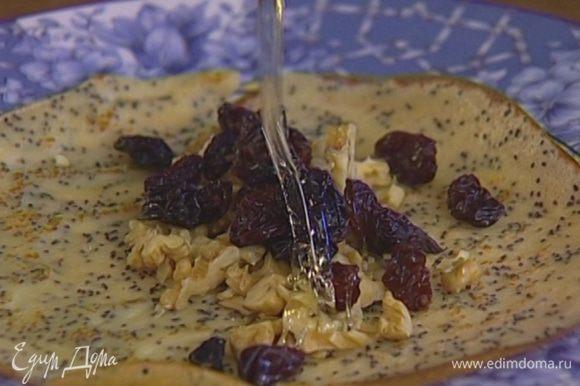 Выложить в центр каждого блина немного изюма и грецких орехов, свернуть трубочкой, полить медом.