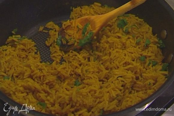 Кинзу мелко порубить, присыпать рис, перемешать и посыпать орехами.