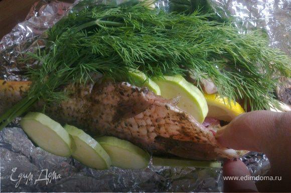Под карпа выкладываем кружочки кабачка,вовонутроь кладем дольки лимона,кабачок.Обкладываем веточками зелени укропа.