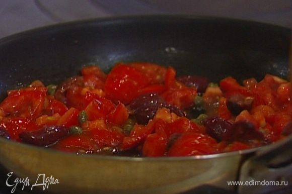 Разогреть в сковороде немного оливкового масла, отправить туда помидоры, оливки и каперсы, добавить томатный соус, все посолить, немного прогреть и снять с огня.