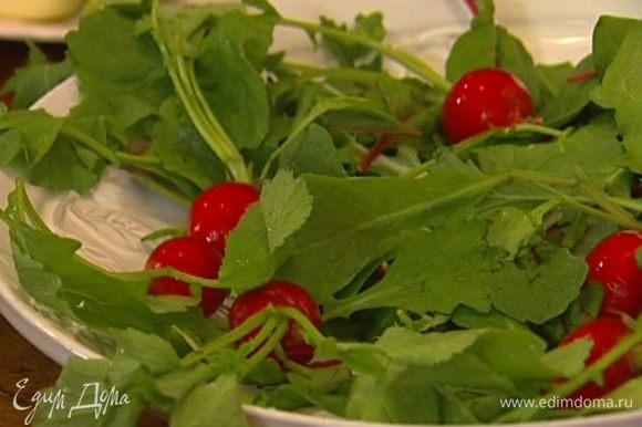 Салатные листья выложить на большое блюдо, сверху разложить редиску, оставив ее целиком и сохранив на ней 2‒3 листика.