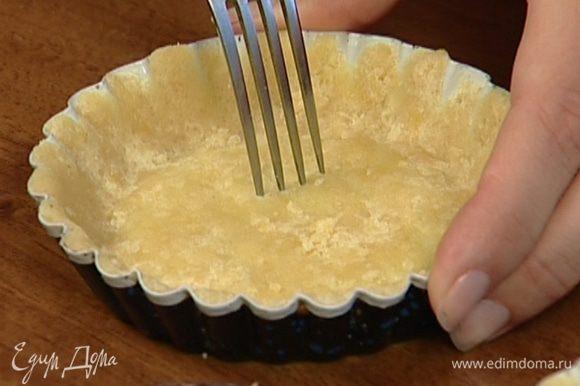 Смазать небольшие формочки оставшимся сливочным маслом, выложить в них тесто и, прижимая пальцами, распределить равномерно по дну и стенкам. Проткнуть тесто в нескольких местах вилкой и выпекать в разогретой духовке 10–15 минут.