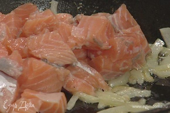 Рыбу нарезать небольшими кубиками (1−1,5 см), выложить в сковороду к луку и жарить пару минут на небольшом огне.