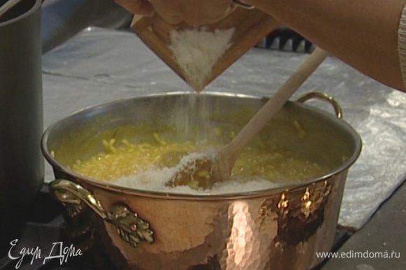 Через 18‒20 минут, когда рис будет почти готов, добавить замоченный в бульоне шафран, оставшееся сливочное масло и половину натертого сыра. На 1 минуту закрыть сковороду крышкой и затем очень энергично все перемешать, почти взбить.