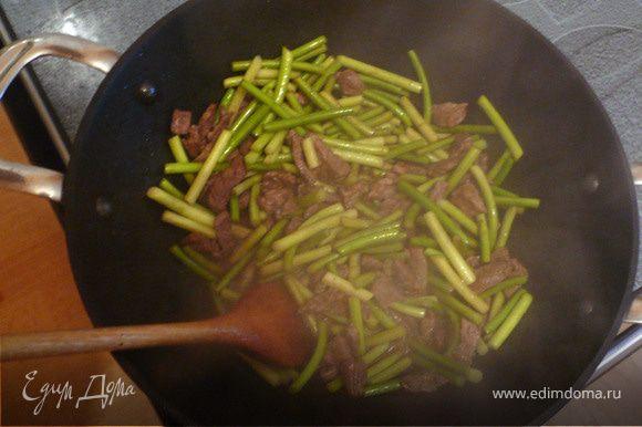 В большой сковороде-вок разогреваем соевое масло. Даже если вы не любите жарить на соевом масле, в данном случае оно придется как нельзя кстати и только улучшит вкус блюда! На разогретом масле в течение трех - пяти минут обжариваем мясо. Затем добавляем побеги и готовим еще примерно 2-3 минуты. Чеснок должен схватиться и начать источать свежий аромат.