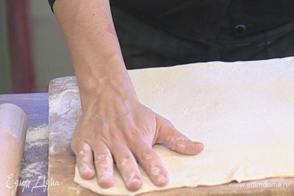 Посыпать поверхность стола мукой, раскатать тесто.