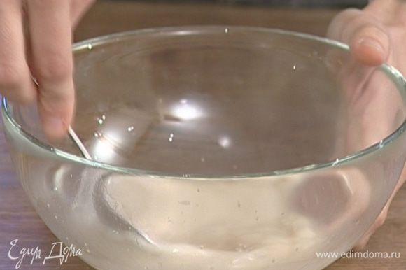 В большую подогретую миску влить 150 мл теплой воды, всыпать дрожжи и сахар.