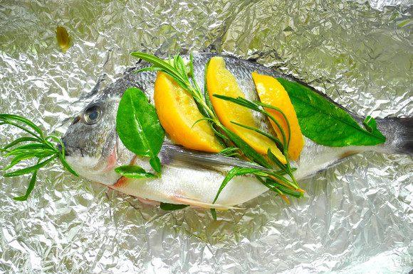 Четвертинку лимона и часть трав положить в пузико. Сверху рыбку надрезать поперек туловища, и положить в разрезики дольки соленого лимона. Сверху украсить травами и листьями лимона. Сбрызнуть оливковым маслом.
