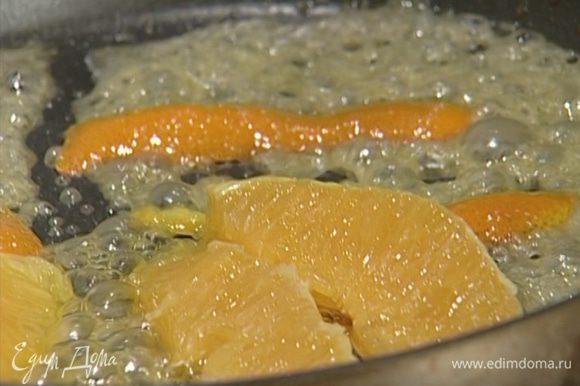 Растопить в сковороде 1 ч. ложку сливочного масла, добавить сахар, цедру и несколько долек апельсина.