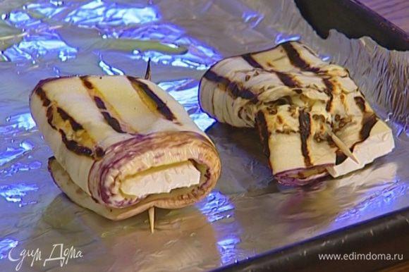На баклажаны положить понемногу сыра, присыпать измельченными орехами, свернуть в рулетики и скрепить зубочистками.