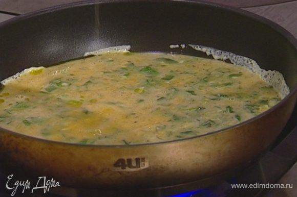 В сковороде с толстым дном разогреть оливковое масло, добавить взбитые яйца с сыром. Уменьшить огонь и дождаться, чтобы омлет схватился.