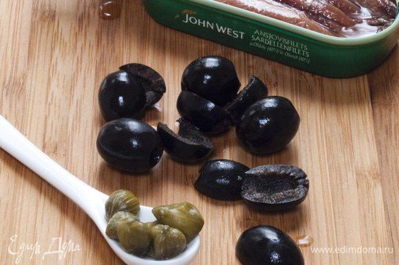 Оливки разломить на половинки и вынуть из них косточки.