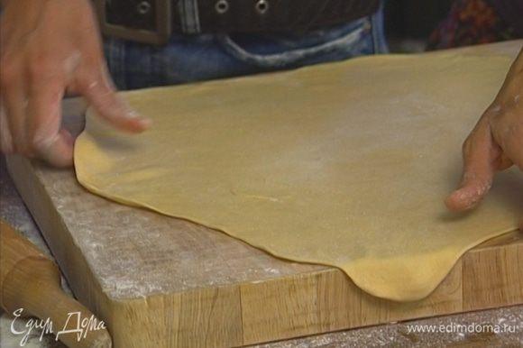 Присыпать рабочую поверхность оставшейся мукой и раскатать тесто как можно тоньше.