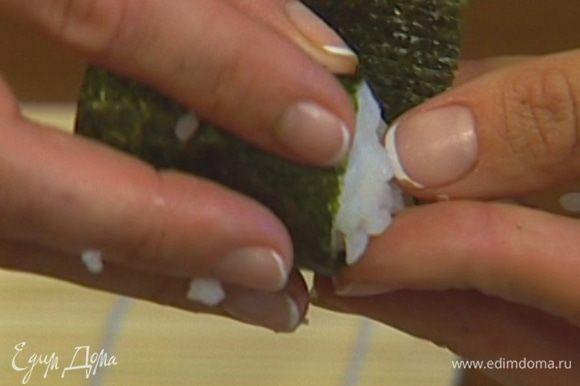 Выложить на полоску нори шарик суши-риса и обернуть ее вокруг риса так, чтобы ролл был слегка ассиметричным. Заправить свободный конец нори внутрь «лодочки» и вдавить его в рис.