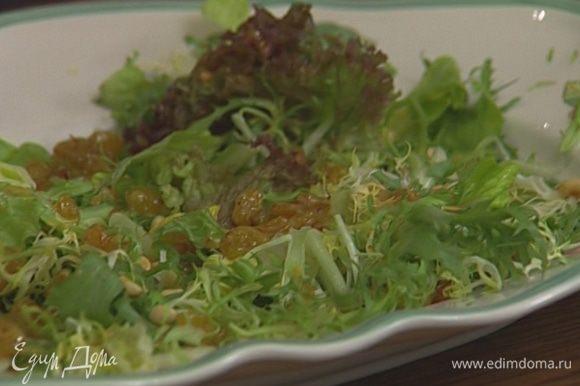 На большое плоское блюдо выложить крупно нарезанные или порванные руками листья салата, присыпать половиной орехов и полить заправкой.
