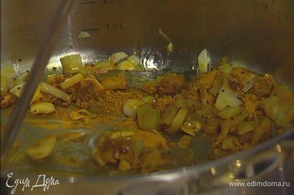 Разогреть в глубокой тяжелой сковороде растительное масло, обжарить лук и чеснок. Добавить в сковороду карри, семена горчицы, куркуму, кардамон и кориандр, все перемешать.