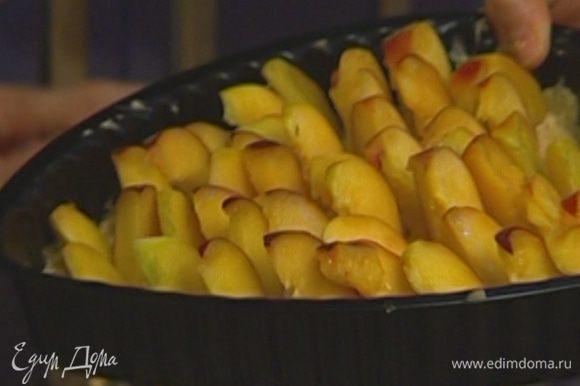 Выложить на пропеченный корж миндальный крем, воткнуть в крем по всей поверхности дольки персиков.