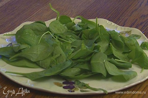 Шпинат разложить на большой тарелке, сбрызнуть лимонным соком и оливковым маслом.