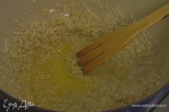 Растопить в глубокой тяжелой кастрюле сливочное масло, всыпать рис, перемешать и прогревать на небольшом огне 2–3 минуты, чтобы рис пропитался маслом.