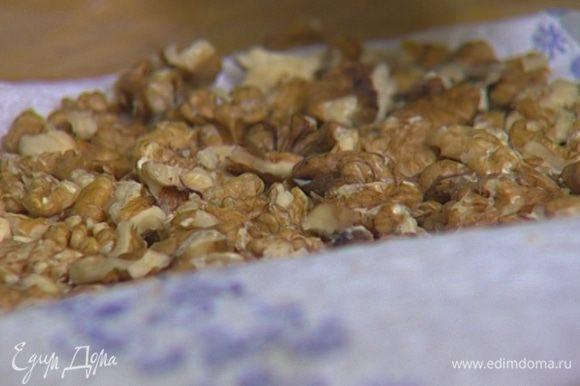 Грецкие орехи завернуть в кухонное полотенце и немного измельчить с помощью скалки.