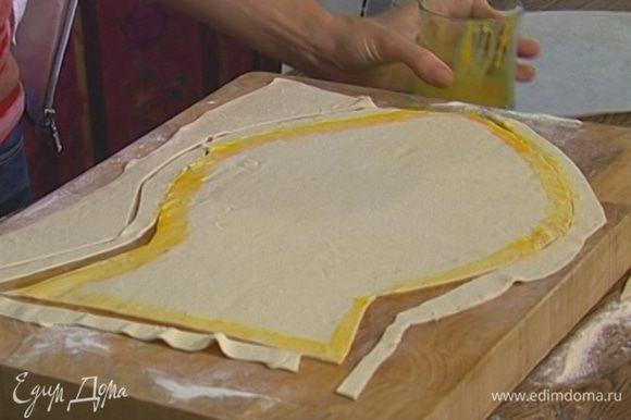 Желток слегка взбить, смазать им тесто и уложить на края «рыбы» полоски теста, чтобы получился бортик.
