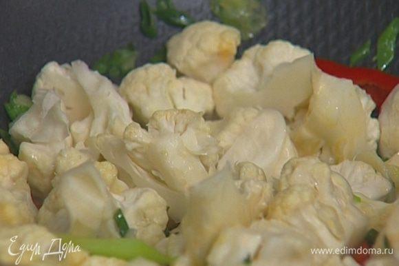 Разогреть в сковороде-вок арахисовое масло, добавить чеснок, чили, зеленый лук, имбирь и цветную капусту, перемешать.
