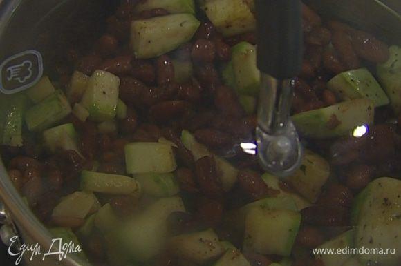 Добавить кабачки, чеснок и отваренную фасоль вместе с водой, в которой она варилась. Посолить и варить все на медленном огне около 10 минут до готовности сельдерея.