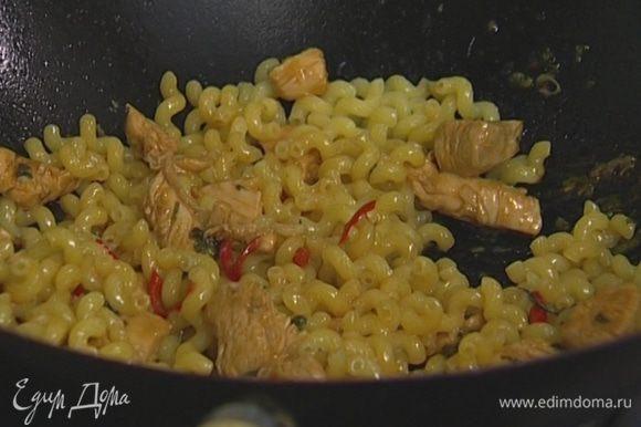 Обжарить в сковороде-вок кусочки курицы вместе с маринадом, добавить макароны, все перемешать.