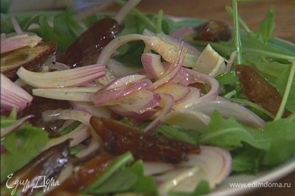 Выложить на блюдо руколу, сверху финики с луком вместе с маринадом и присыпать все зеленым луком.