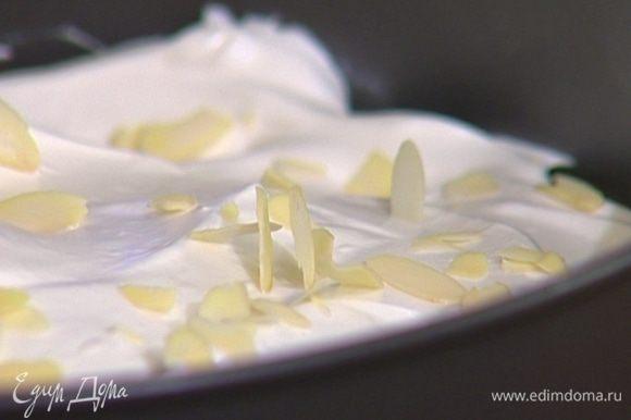 Приготовить меренги: белки взбить со щепоткой соли и 200 г сахара в крепкую пену и выложить сверху на тесто в обеих формах. Присыпать миндалем и выпекать в разогретой духовке 30–35 минут.