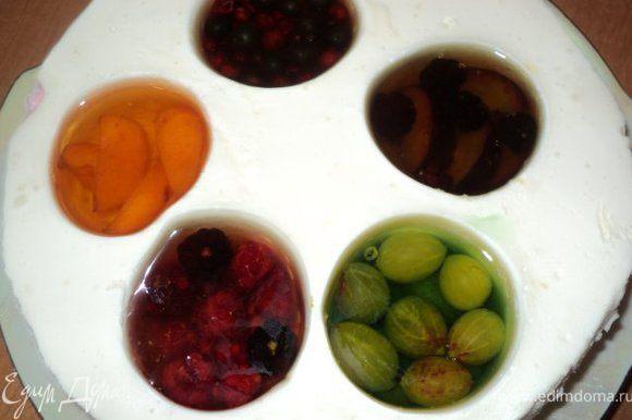 Вынуть торт из холодильника. В стаканы по очереди налить немного горячей воды, чтобы было легче вынуть их из формы. В образовавшиеся выемки положить по немного ягод и фруктов, залить охлажденным желе соответствующего цвета и поставить в холодильник для застывания на 2 часа ( немного желе оставить ).