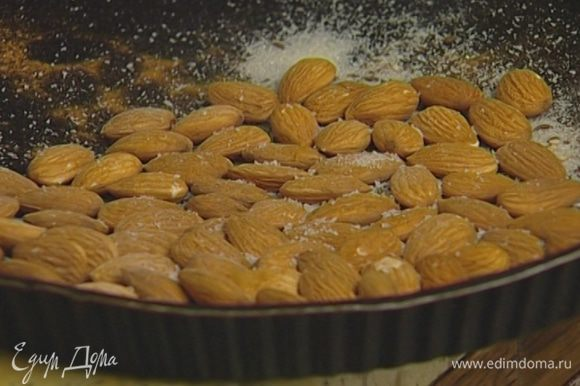 Миндаль поместить в форму для выпечки, посыпать кунжутным семенем, тмином, корицей, сахаром, измельченным пеперончино, солью, полить 1‒2 ч. ложками орехового масла и все перемешать.
