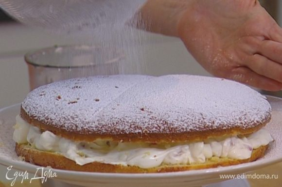 Нарезанную клубнику перемешать со сливками и выложить на одну половину бисквита, сверху накрыть второй половиной.