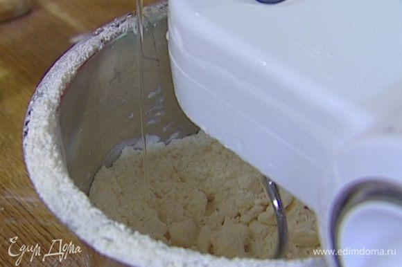 Когда масса приобретет консистенцию мелкой крошки, добавить яйцо, желток и 80 мл ледяной воды.
